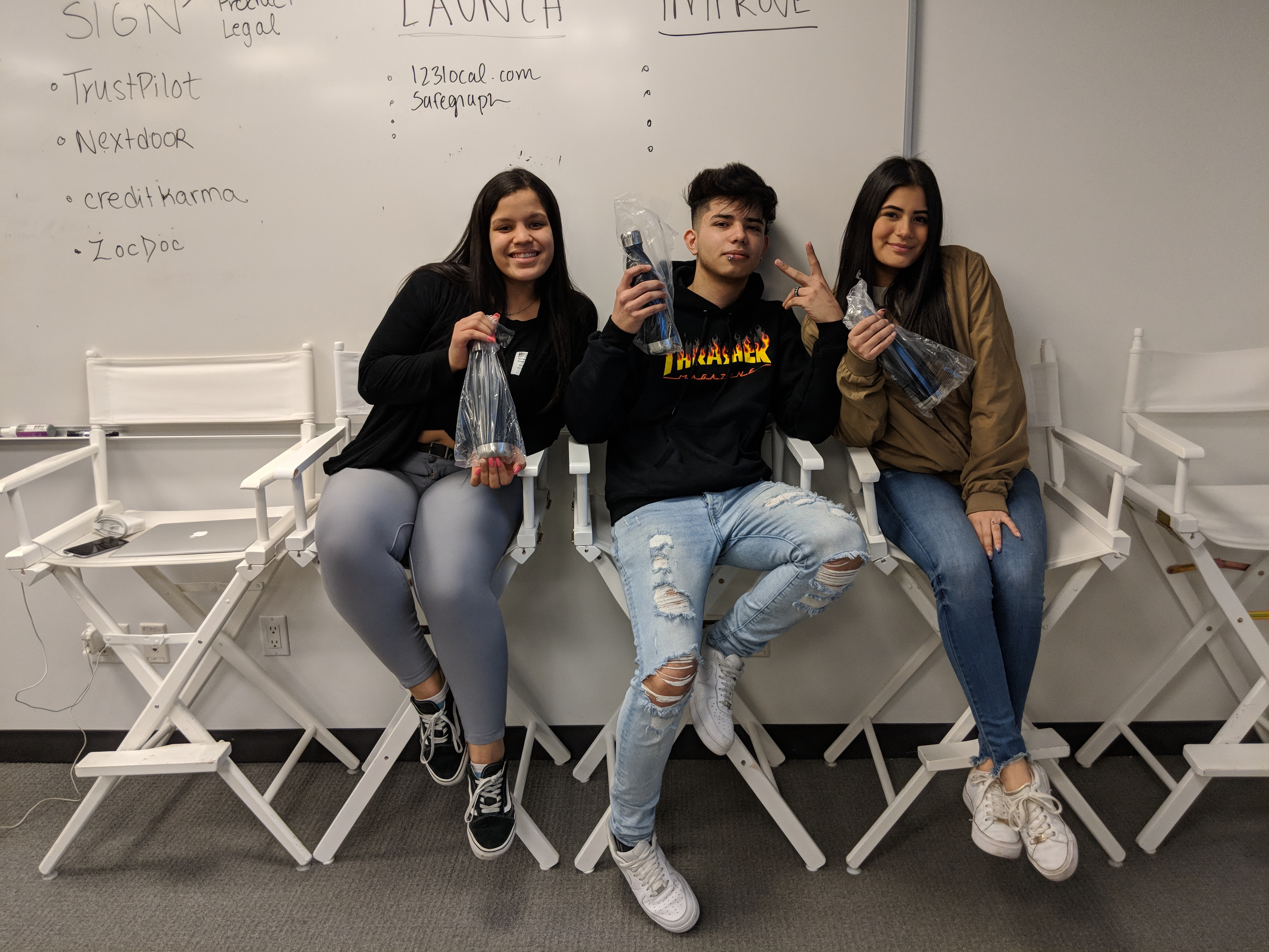 3 students posing with bottles
