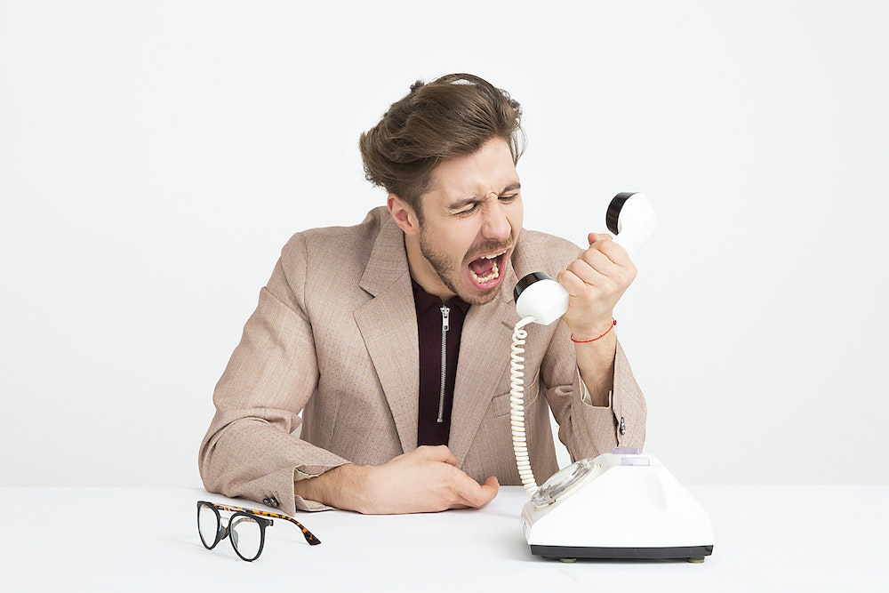Man yelling down the phone